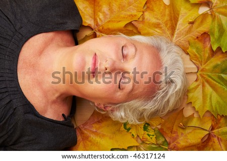 Happy senior woman with many colorful maple leaves