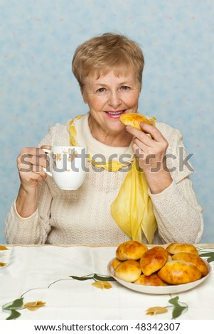 Happy senior woman with pie and cup - stock photo