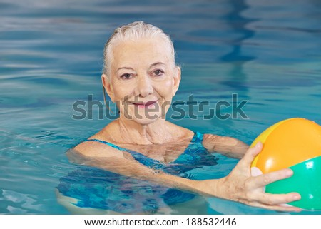 Happy senior woman with water ball in swimming pool doing aqua fitness - stock photo