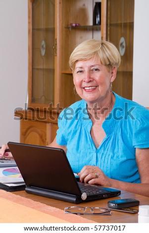 happy senior woman working on home finance - stock photo