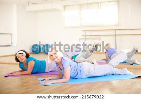 Happy senior women doing physical exercise in sport gym  - stock photo