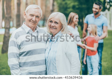 Happy seniors. Happy senior couple bonding and looking at camera while other family members standing in the background - stock photo