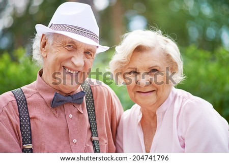 Happy seniors in smart casual looking at camera outside - stock photo