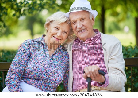Happy seniors sitting in the park and looking at camera - stock photo