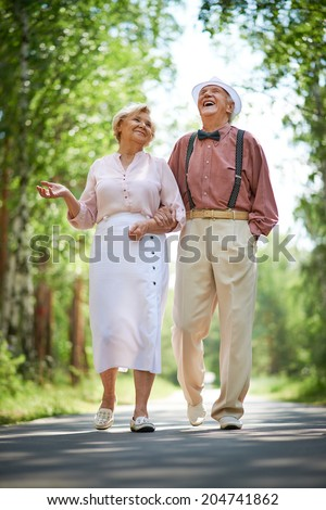 Happy seniors talking and having fun while taking a walk in the park - stock photo