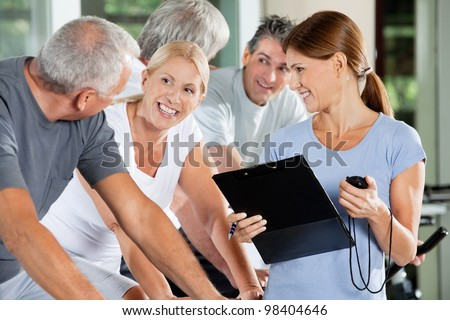 Happy seniors with fitness trainer in a gym - stock photo