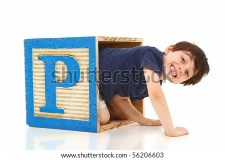 Happy seven year old french american boy crawling out of a giant letter P alphabet block over white. - stock photo