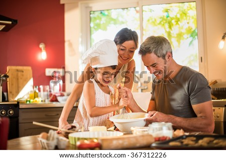 Happy seven years old girl with chef hat is cooking with her mother and grey haired father in a luminous kitchen. They are mixing a preparation in a large bowl, on a wooden table full of ingredients. - stock photo