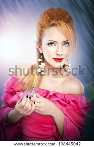 Happy sexy beautiful  blond girl in pink  dress with hairstyle and bright makeup and perfume bottle. Romantic lady in pink dress and long blond hair have final preparation.Blond Woman applying perfume - stock photo