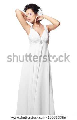 Happy sexy beautiful bride brunette girl in white wedding dress with hairstyle and bright makeup with flower in hair isolated on white - stock photo