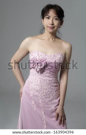 Happy sexy beautiful bride girl in pink wedding dress �gray background  - stock photo