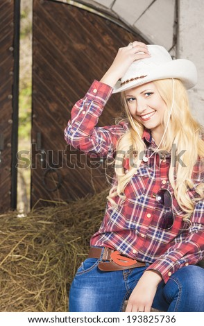 Happy Sexy Blond Cowgirl Smiling inside of the Farm House. Vertical Image - stock photo