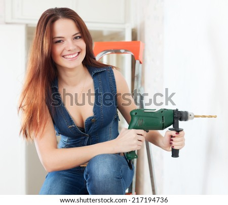 Happy sexy girl with drill  makes repairs at home - stock photo
