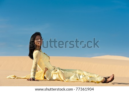 Happy sexy lady sitting on sand - stock photo