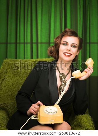 happy sexy pin up girl talking on retro telephone and sitting on green armchair - stock photo