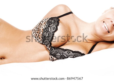 happy sexy wet busty girl in black lingerie and lying on bed - stock photo