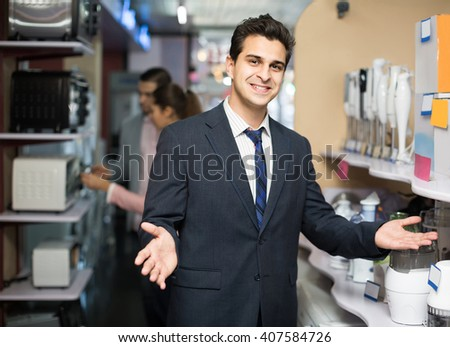 happy shop assistant working with customer at small household appliances section. focus on seller - stock photo