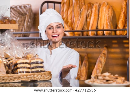 Happy shopgirl working in bakery with bread and different pastry - stock photo