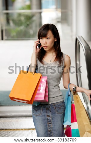 Happy Shopper Smiling with Shopping Bags on Phone - stock photo