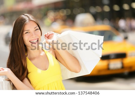 Happy shopper woman holding shopping bags, New York City, Manhattan, USA. Beautiful fresh joyful female model walking in street in summer dress with yellow taxi cab in background. Multiracial girl. - stock photo