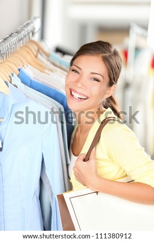 Happy shopper woman shopping for clothes in clothing store looking at camera smiling joyful. Mixed race Asian Chinese / Caucasian young woman. - stock photo