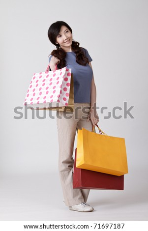 Happy shopping Chinese lady holding bags and smiling. - stock photo