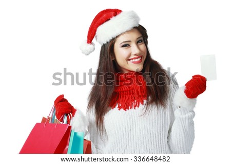 Happy shopping Christmas woman with bags holding business or credit card - stock photo