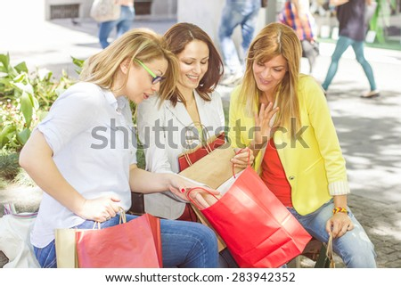 Happy Shopping Female Friends with bags on the street bench.Group of caucasian women purchasing in the city. - stock photo