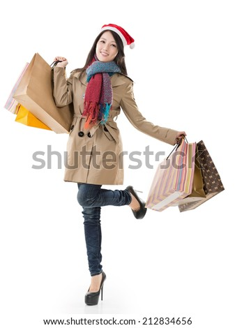 Happy shopping girl holding bags and gift box, wearing Christmas hat ,full length portrait isolated on white background. - stock photo