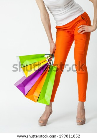 Happy shopping! Unrecognizable woman in orange pants holding multicolored shopping bags - stock photo