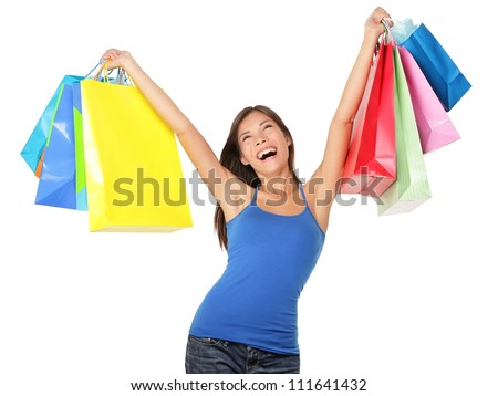 Happy shopping woman excited and cheerful in joyful bliss. Shopper holding many colorful shopping bags isolated on white background . Elated beautiful mixed race Caucasian / Asian Chinese female model