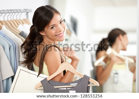 Happy shopping woman in clothing store smilng bolding shopping bags and clothes dress. Beautiful Eurasian model inside - stock photo