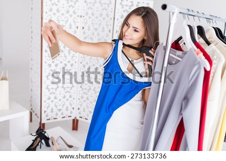 Happy shopping woman is taking a snapshot for social networking in the shopping mall - stock photo