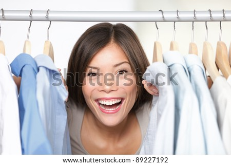 Happy shopping. Woman shopper or shop owner peeking out through clothing in clothes rack. Excited multicultural Asian / Caucasian woman smiling happy in shop. - stock photo