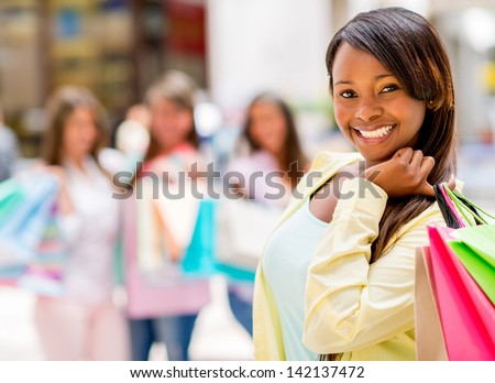 Happy shopping woman smiling at the mall holding bags - stock photo