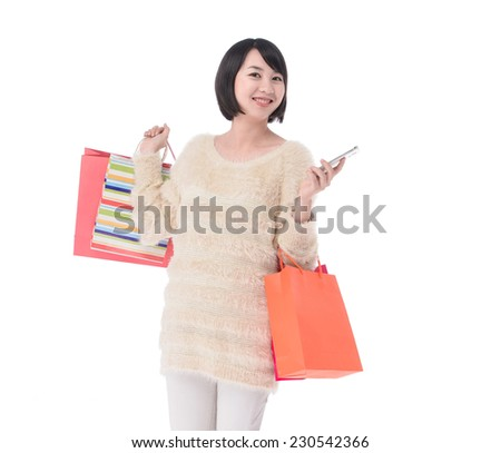 Happy shopping woman texting on her cell phone - stock photo