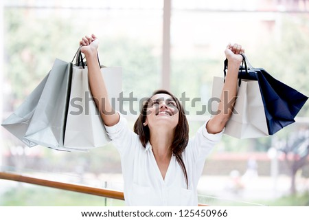 Happy shopping woman with arms up holding bags - stock photo