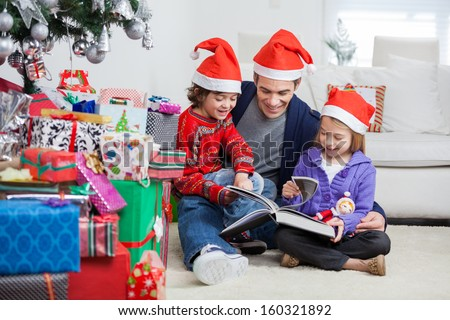 Happy siblings and father in Santa hats reading book while sitting by Christmas presents at home - stock photo