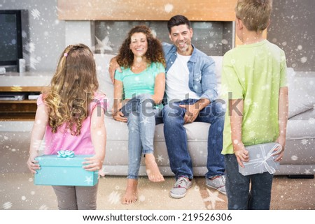 Happy siblings hiding presents behind their back from their parents against snow - stock photo