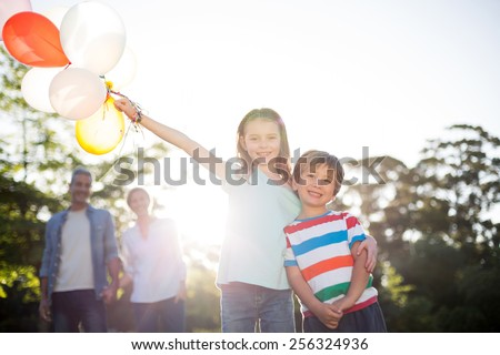 Happy siblings holding balloons at the park on a sunny day - stock photo