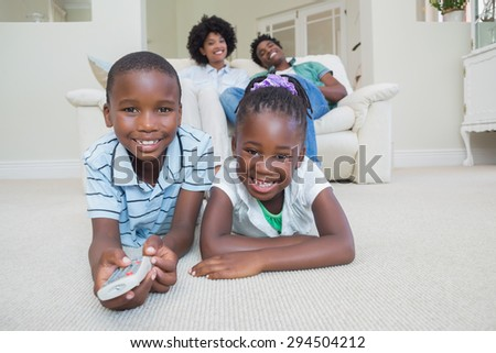 Happy siblings lying on the floor watching tv at home in the living room - stock photo