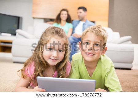 Happy siblings lying on the rug using a tablet at home in living room - stock photo