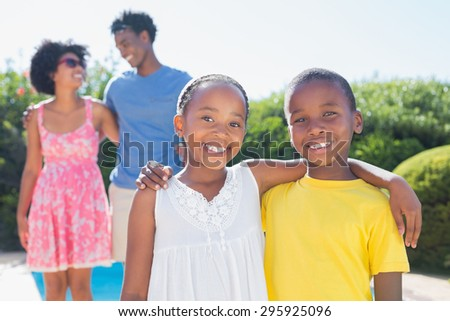 Happy siblings smiling at camera in the garden at home - stock photo