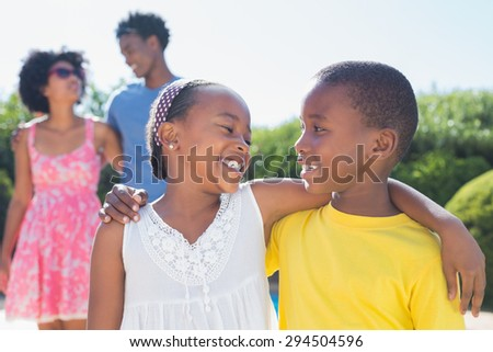 Happy siblings smiling at each other in the garden at home - stock photo