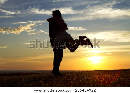 Happy silhouette couple embracing as the answer is yes to a marriage proposal against the background of sunset - stock photo