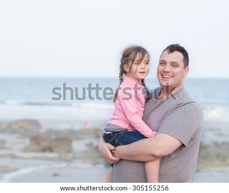 happy single parent holding his daughter during their first vacation together - stock photo