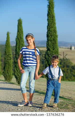 Happy sister and brother having fun on vacations in Tuscan against cypress alley background. Vertical view - stock photo