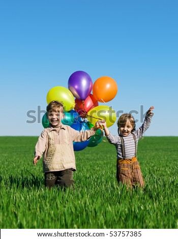 Happy sister and brother with balloons walking on spring field - stock photo