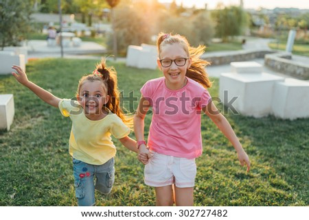 happy sisters are running and smiling  in the park - stock photo