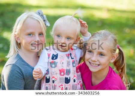 Happy sisters are smiling outside in the park. - stock photo
